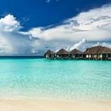 Härlig strand med vattenbungalower Royaltyfri Foto