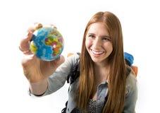 Härlig studentflicka som rymmer det lilla världsjordklotet i hennes hand som väljer feriedestinationen i loppturismbegrepp Royaltyfria Foton
