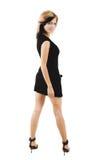härlig svart gullig klänning som poserar den stilfulla kvinnan Fotografering för Bildbyråer