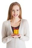 Härlig tillfällig kvinna som rymmer liten gåva i händer. Royaltyfri Bild