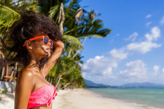Härlig tonårs- svart flicka med långt lockigt hår i solglasögon Arkivbild
