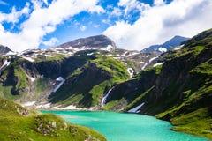 Härlig turkossjö nedanför de höga bergen Arkivbilder