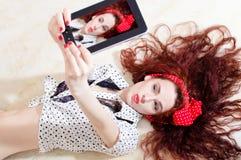 Härlig ung attraktiv kvinnautvikningsbrudflicka som ligger och tar som är selfy, eller selfiebild på den digitala minnestavladato Royaltyfri Bild