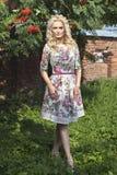 Härlig ung blond kvinna som går i parkera Royaltyfri Bild