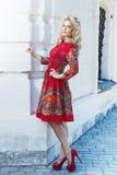 Härlig ung blond kvinna som går runt om stadsgatorna Arkivfoto