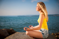 Härlig ung blond kvinna som mediterar på en strand på soluppgång in Royaltyfria Bilder