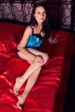 Härlig ung brunettflicka i sovrummet i blå damunderkläder med ett leende Royaltyfria Bilder