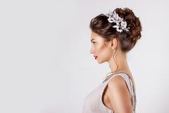 Härlig ung flicka i bilden av bruden, härlig bröllopfrisyr med blommor i hennes hår, frisyr för brud Fotografering för Bildbyråer