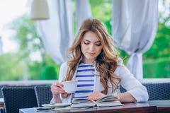 Härlig ung flicka i utomhus- kafé läsande a Arkivbilder