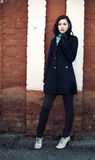 Härlig ung fundersam flicka nära tegelstenväggen Arkivfoto