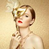 Härlig ung kvinna i mystisk guld- Venetian maskering Arkivbilder
