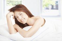 Härlig ung kvinna i sovrummet Arkivfoto