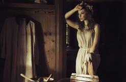 Härlig ung kvinna på en gammal lantlig stuga Arkivfoto