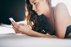 Härlig ung kvinna på säng som smsar med hennes mobiltelefon Royaltyfri Foto