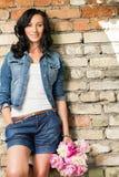 Härlig ung kvinna på tegelstenväggen Royaltyfria Foton