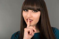 Härlig ung kvinna som gör en gest för tystnad, genom att rymma ett finger Royaltyfri Foto
