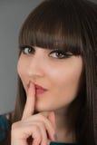 Härlig ung kvinna som gör en gest för tystnad, genom att rymma ett finger Fotografering för Bildbyråer