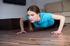 Härlig ung kvinna som hemma gör push-UPS Arkivfoton