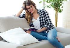Härlig ung kvinna som läser en bok i soffan Arkivbild