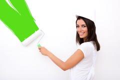Härlig ung kvinna som målar en lägenhet Arkivfoto