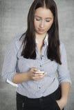 Härlig ung kvinna som skriver ett textmeddelande Royaltyfri Fotografi