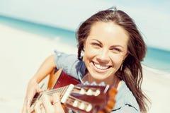 Härlig ung kvinna som spelar gitarren på stranden Royaltyfria Foton