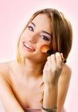 Härlig ung kvinna som sätter på makeup över en rosa bakgrund Royaltyfri Foto