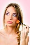 Härlig ung kvinna som sätter på makeup över en rosa bakgrund Arkivbild