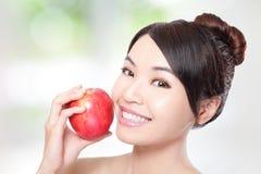 Ung kvinna som äter det röda äpplet med vård- tänder Arkivbild