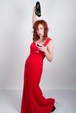 Härlig ung sexig slank rödhårig flicka bärande höga häl för en åtsmitande siden- röd klänning, i alkoholiserat rus Royaltyfri Fotografi