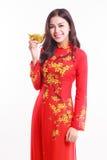 Härlig vietnamesisk kvinna med röd ao dai som rymmer den lyckliga prydnaden för nytt år - bunt av guld Arkivfoto