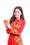 Härlig vietnamesisk kvinna med röd ao dai som rymmer den lyckliga prydnaden för nytt år - bunt av guld Arkivfoton