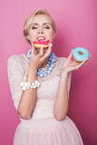 Härliga blonda kvinnor som äter den färgrika efterrätten skjutit mode soft för fält för färgpildjup grund Fotografering för Bildbyråer