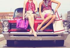 Härliga damer lägger benen på ryggen att posera i en retro bil för tappning Arkivbilder