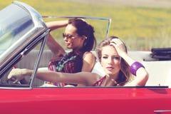Härliga damer med solexponeringsglas som rider en retro bil för tappning Royaltyfri Bild