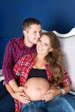 Härliga gravida par som hemma kopplar av på soffan tillsammans Lycklig familj, man och kvinna som förväntar ett barn Royaltyfri Fotografi