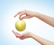 Härliga kvinnliga händer med ett äpple på ljus - blått Arkivfoto