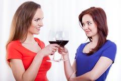 Härliga kvinnliga vänner som lyfter exponeringsglas av rött vin Royaltyfri Bild