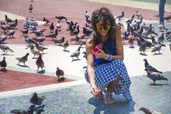 Härliga matande duvor för ung kvinna i Barcelona, Spanien Royaltyfri Foto
