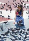 Härliga matande duvor för ung kvinna i Barcelona, Spanien Arkivbild