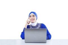 Härliga muslim som tänker med den isolerade bärbara datorn - Arkivbild