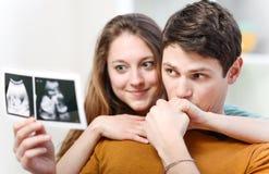 Härliga par som håller ögonen på med sinnesrörelseultraljudbilder av deras, behandla som ett barn Arkivbilder