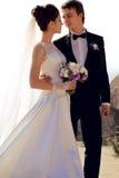 härliga par ursnygg brud i bröllopsklänningen som poserar med den eleganta brudgummen på havskostnad Royaltyfria Bilder