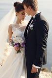 härliga par ursnygg brud i bröllopsklänningen som poserar med den eleganta brudgummen på havskostnad Royaltyfria Foton