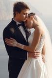härliga par ursnygg brud i bröllopsklänningen som poserar med den eleganta brudgummen på havskostnad Royaltyfri Fotografi