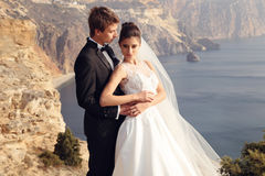 härliga par ursnygg brud i bröllopsklänningen som poserar med den eleganta brudgummen på havskostnad Arkivfoton