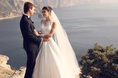härliga par ursnygg brud i bröllopsklänningen som poserar med den eleganta brudgummen på havskostnad Royaltyfri Bild