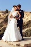härliga par ursnygg brud i bröllopsklänningen som poserar med den eleganta brudgummen på havskostnad Arkivfoto