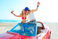 Härliga partiflickor som dansar i en bil på stranden Royaltyfri Foto