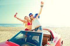 Härliga partiflickor som dansar i en bil på stranden Fotografering för Bildbyråer